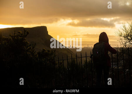 A tourist enjoys the view of Arthur's Seat under a dramatic sky at dawn - Stock Image