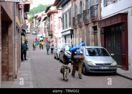 Pilgrim with a dog leaving early morning on their way to Santiago on the way of St-James, streets of St-jean-pied-de-port, France, June 2019 - Stock Image