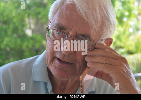 Senior man on a mobile phone, talking and looking concerned - Stock Image