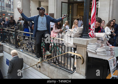As activists with Extinction Rebellion protest about climate change in a blocked-off Oxford Circus a newspaper vendor sings to the DJ's music, on 17th April 2019, in London, England. - Stock Image