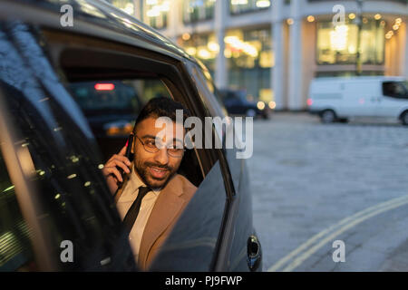 Businessman talking on smart phone in crowdsourced taxi - Stock Image