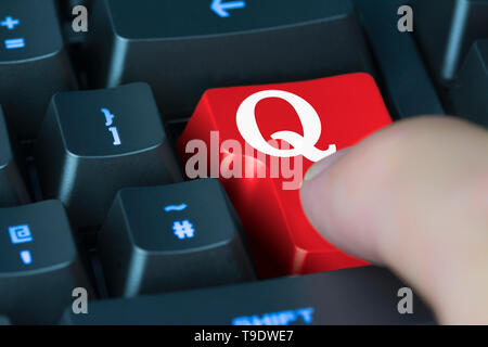 Finger pressing button on a computer keyboard to load the Quora app or website, a website for online knowledge sharing. - Stock Image