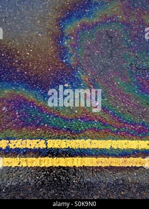 Abstract photo of details of road markings and oil spill. - Stock Image