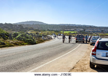 Cars and cyclists on Sunset Drive by Asilomar State Beach in Pacific Grove, California, USA. - Stock Image