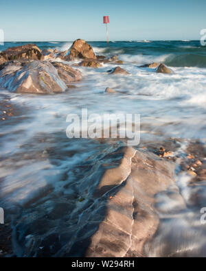 stormy sea with waves crashing over rocks at the seaside - Stock Image