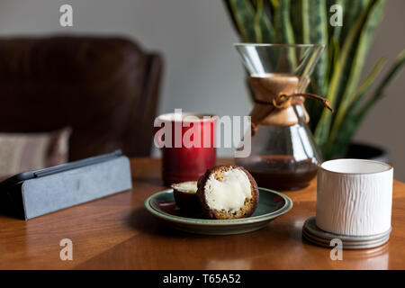 A modern living room coffee table with a coffee cup, book, tablet, and a muffin on it. - Stock Image