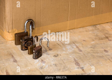 A line of old rusting unlocked padlocks arranged large to small. - Stock Image