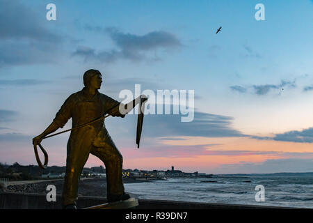 Newlyn, Cornwall, UK. 22nd November 2018. UK Weather. Strong cold winds were hitting the seafront at Newlyn this morning at sunrise. In the foreground Tom Leaper's Fishermen's memorial statue. Credit: Simon Maycock/Alamy Live News - Stock Image