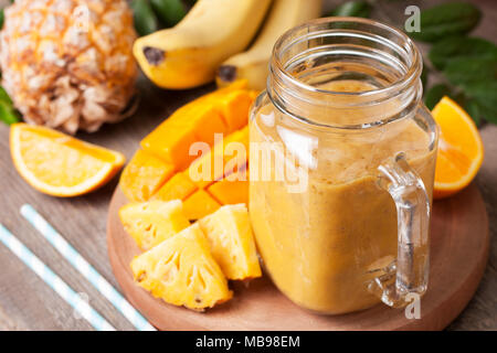 smoothie with tropical fruits: mango, banana, pineapple in a Mason jar on old wooden background - Stock Image