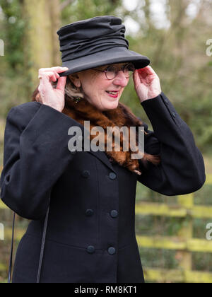 A smart lady in old-fashioned coat and hat with a fox fur stole at a historic re-enactment. - Stock Image