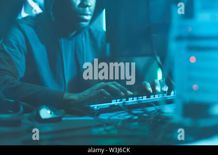 Close-up of concentrated black security hacker in hoodie sitting at table with cables and typing on keyboard while hacking computer system - Stock Image