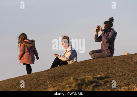 People sitting and enjoying the late evening sunlight. - Stock Image