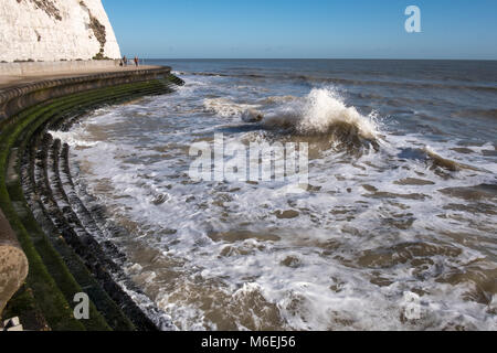 The high tide on the waterfront path near Broadstairs with the sea lapping on the promenade steps to the sandy beach. - Stock Image