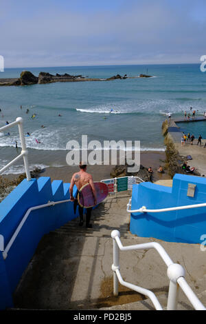 Bude, Cornwall, UK. Surfer walks towards Bude's semi-natural sea bathing pool - Stock Image