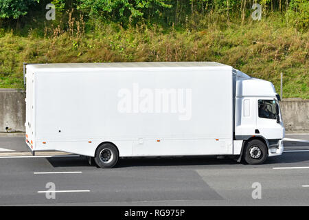 Side view of a clean unmarked all white hgv  lorry truck van transport with cab & driver without any advertising driving along M25 motorway England UK - Stock Image