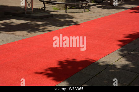 red carpet in the pedestrian zone for vip, rolled out red carpet by day no people for an evening event - Stock Image