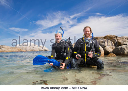 Couple in wetsuits going ocean scuba diving from rocky beach and smiling at camera - Stock Image