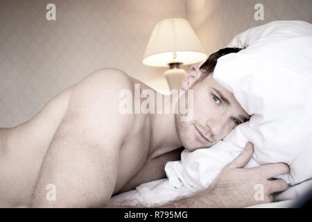 Good looking nude muscular man with blue eyes lying on hotel bed sheets looking at camera - Stock Image