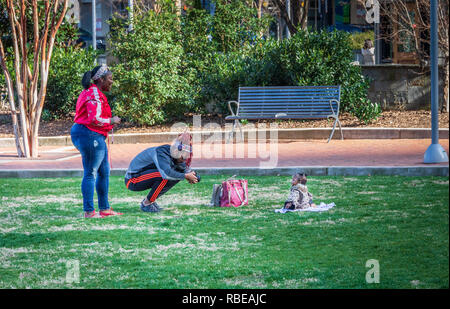 CHARLOTTE, NC, USA-1/8/19: A young black couple photographing infant in Romare Park in uptown. - Stock Image