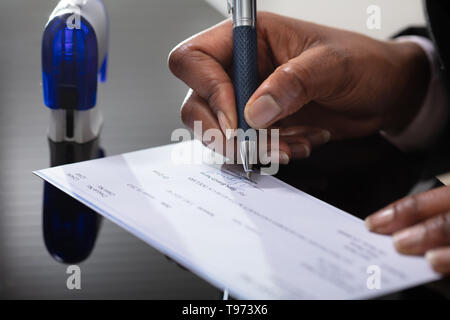 Photo Of Businessperson's Hand Signing Cheque With Pen - Stock Image