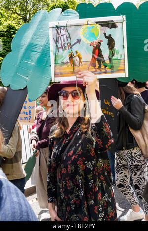 London, UK. 12th May 2019. A woman holds up a poster on the XR International Mothers Day March by several thousand mothers, children and some fathers from Hyde Park Corner to a rally filling Parliament Square, backing Extinction Rebellion's call for the drastic and urgent action needed to avert the worst consequences of climate change, including possible human extinction. Our politicians have declared a climate emergency but now need to take real action rather than continuing business as usual which is destroying life on our planet. Peter Marshall/Alamy Live News - Stock Image