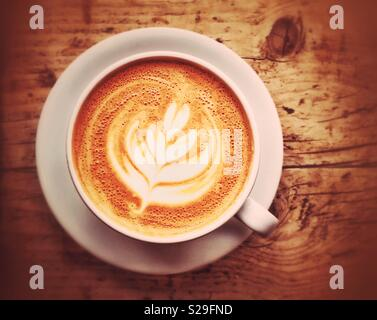 An overhead picture of a large white cup of Latte Coffee. The cup and saucer sit on a wooden table. There is space for copy/text. Photo Credit - © COLIN HOSKINS. - Stock Image