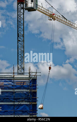 A tower construction crane working in high wind amid a blue cloudy sky on new home units building site, Australia, November 2018 update  e151ene. - Stock Image