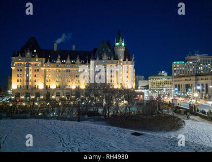 Chateau Laurier at Night from Parliament Hill: The iconic hotel floodlit on a cold winter night with Wellington's street lights and snowy ground below. - Stock Image