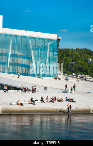 Opera House Oslo, waterfront view in summer of people sunbathing or walking on the vast access ramp leading to the roof of the Oslo Opera House. - Stock Image