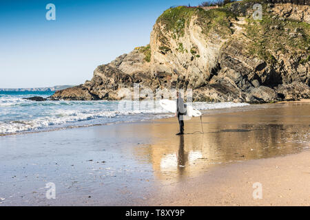 A surfer carrying his surfboard and standing on the shoreline on Great Western Beach in Newquay in Cornwall. - Stock Image