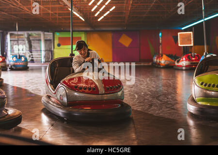 Happy young woman driving a bumper car at amusement park - Stock Image