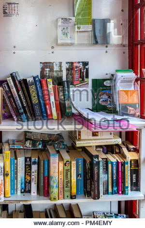 An old BT red telephone box in use as an informal library in the New Forest village of Fritham, Hampshire, UK - Stock Image