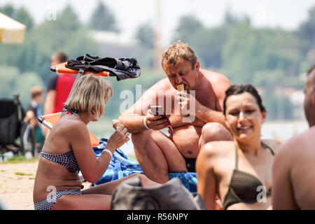 Garda Lake , Italy 17 july 2018 : a man uses the phone and eats ice cream during a hot summer day at the beach . - Stock Image