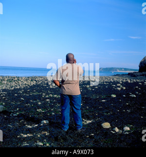 Man talking on mobile phone at beach near Tenby Pembrokeshire Wales UK  KATHY DEWITT - Stock Image