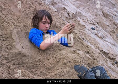 Young teenage boy covering himself in sand while fully dressed, winter at Marengo beach, Vic, Australia. - Stock Image