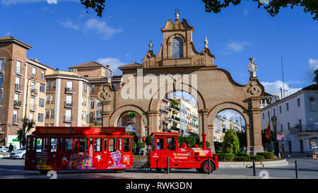 Bright red passenger vehicle as a tour train on a street in a Spanish town; Antequera, Malaga, Spain - Stock Image