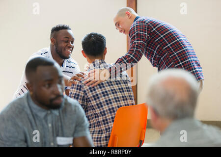 Men talking, comforting in group therapy - Stock Image