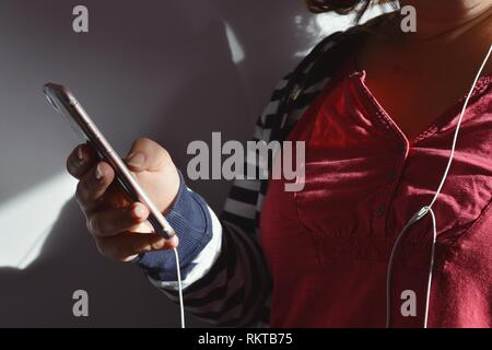 Millennial woman, smartphone in hand with headphone wires, listening to music - Stock Image