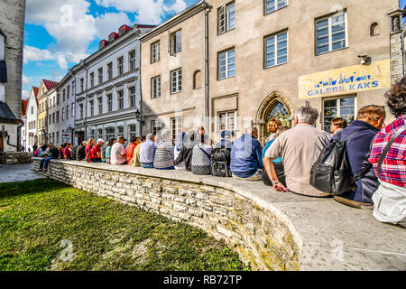 A tour guide and her group of tourists site on a wall in the historic old town center of Tallinn, Estonia. - Stock Image