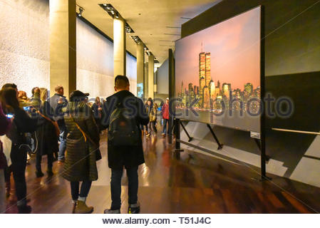 Inside of the National September 11 (9/11) Memorial and Museum. Tourists watching a documentary on a large screen - Stock Image
