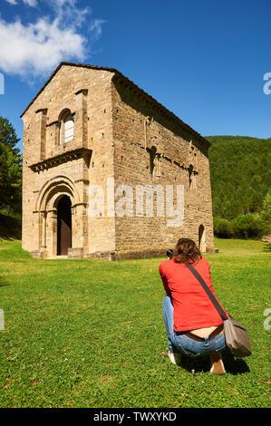 Young woman photographing the XI century romanesque church of Santa María de Iguácel in Garcipollera valley (Larrosa, Huesca, Aragón, Pyrenees,Spain) - Stock Image