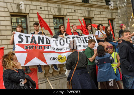 London, UK. 13th October 2018. People sit on the wall with the GIK-DER banner 'Stand Together !' at  the rally in London to oppose racism  and fascism close to where the racist, Islamophobic DFLA were ending their march on Whitehall bringing together various groups to stand in solidarity with the communities the DFLA attacks. The event was organised by Stand Up To Racism and Unite Against Fascism. Peter Marshall/Alamy Live News - Stock Image