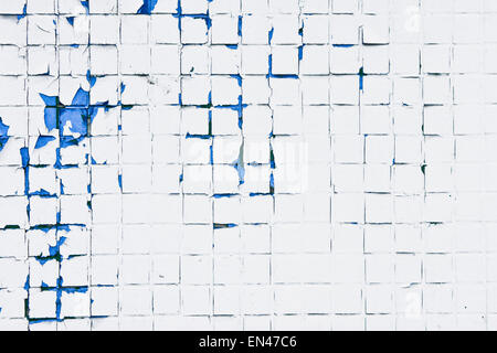 Peeling paint on a wall of tiles as a background image - Stock Image