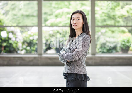 Portrait of an Asian businesswoman in the lobby of a convention center. - Stock Image