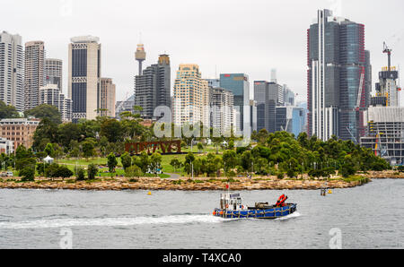 A working boat passes Baragaroo Reserve in Sydney Harbour, with the Sydney skyline behind. - Stock Image