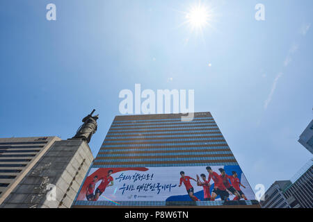 Statue of Admiral Yi Sun-Shin next to large FIFA World Cup banner affixed to building in support of South Korean national team. In Gwanghwamun, Seoul, - Stock Image