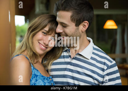 Young woman leaning head on boyfriend's shoulder, portrait - Stock Image