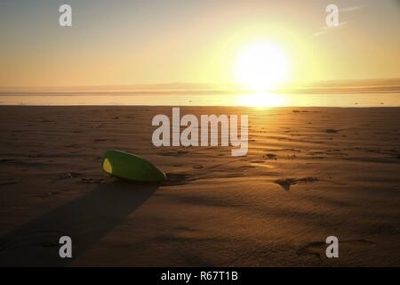 Discarded plastic bottle washed up by Atlantic Ocean on a beach in Morocco at sunset - Stock Image