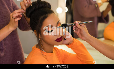 Hairstylist and make-up artist makeup and updo for stylish young African-American woman in beauty parlor. Rich colors. Party image. Beauty industry - Stock Image