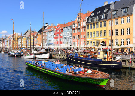 Nyhavn Copenhagen on a summer's day with tourists taking a boat trip - Stock Image